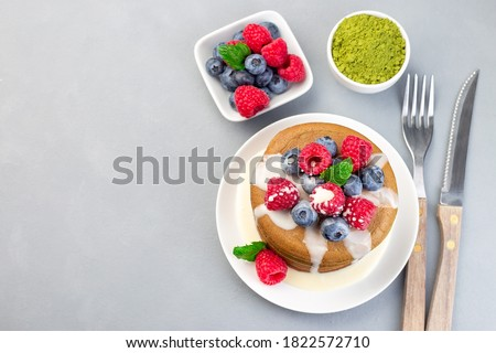 Matcha pancakes served with condensed milk, blueberry and raspberry on a white plate, horizontal, top view, copy space Royalty-Free Stock Photo #1822572710