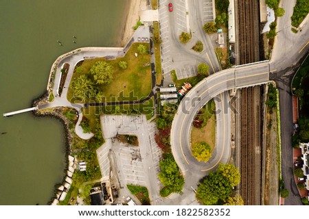 A top-down shot over a curved roadway, which is the entrance and exit for Waterfront Park in Dobbs Ferry, NY. It looks like the breast cancer ribbon. It is a cloudy morning and the park is empty. Royalty-Free Stock Photo #1822582352
