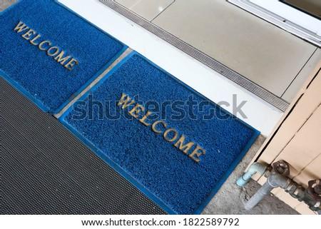 Welcome blue mat in front of door. #1822589792