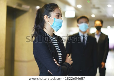 Office workers wearing a mask and keep distancing while waiting the elevator. for prevent infection and reduce spread of Covid-19 virus