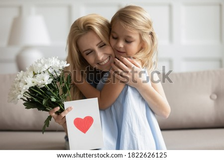 Thank you, my dear. Adorable millennial mom sitting on couch laughing happy embracing tight small child girl holding flowers and handmade greeting card with heart symbol and best wishes on Mothers Day