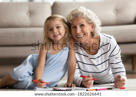 Portrait of happy senior grandma and little girl relaxing on heated floor drawing pictures, hoary old lady art therapist or teacher and small kid patient or pupil coloring paintings looking at camera