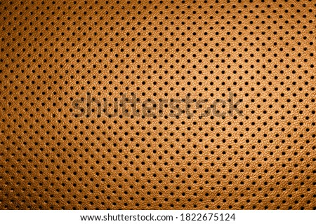 Modern luxury car brown leather interior. Part of perforated orange car seat details. Perforated leather texture background. Texture, artificial leather with stitching. Perforated leather seats #1822675124