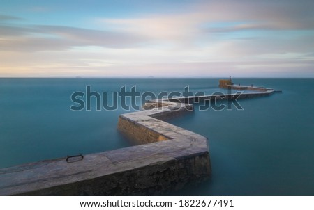 A long exposure shot of the zigzag breakwater at St Monans during some stormy weather - the long exposure smooths out the water giving the appearance of calm Royalty-Free Stock Photo #1822677491