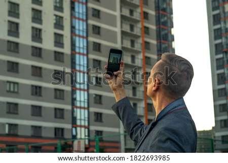 A man takes photos on his phone of a multi-storey residential building. Buying real estate
