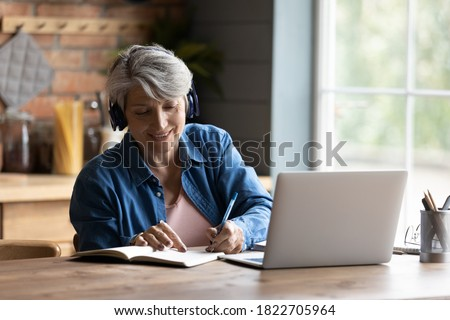 Modern elderly grey-haired 60s woman in headphones take online course or training on computer at home. Smart mature Caucasian female in earphones watch webinar make note study distant on laptop. Royalty-Free Stock Photo #1822705964