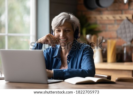 Smiling modern mature 60s Caucasian woman in earphones look at laptop screen watch webinar online at home. Happy senior grey-haired female have fun study on internet. Elderly technology concept. Royalty-Free Stock Photo #1822705973