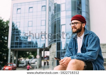Cheerful bearded hipster male relaxed sitting in the city, holding smartphone, smiling and looking away. Blue color scheme.