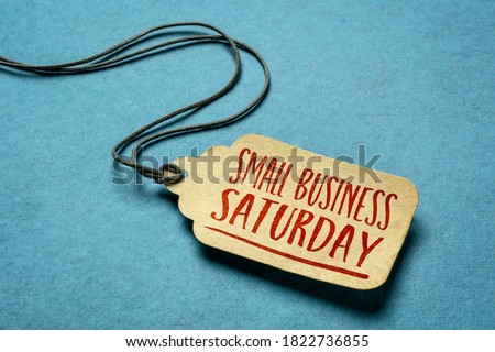 Small Business Saturday sign - a paper price tag with a twine against blue paper background, local holiday shopping concept Royalty-Free Stock Photo #1822736855