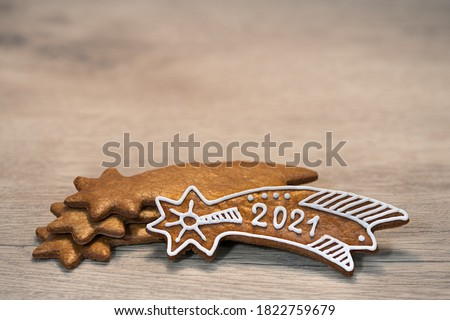 New Year 2021 on ornate gingerbread Bethlehem star for good luck laid on wood background. Gold baked Christmas cookie decorated by sugar icing. Stacked sweets in artistic still life. Selective focus. Royalty-Free Stock Photo #1822759679