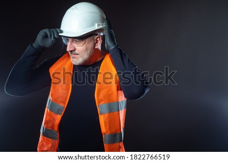 Portrait of the Builder on a dark background. A man in an orange vest puts a white construction helmet on his head. Construction uniforms. Jobs at the construction site. Place for text. Royalty-Free Stock Photo #1822766519