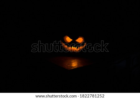 Halloween pumpkin smile and scary eyes for party night. Close up view of scary Halloween pumpkin with eyes glowing inside at black background. Selective focus