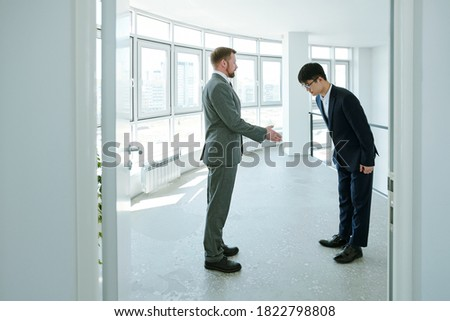 Young successful businessman in formalwear looking at his Asian business partner making bow while greeting him in corridor of office center Royalty-Free Stock Photo #1822798808