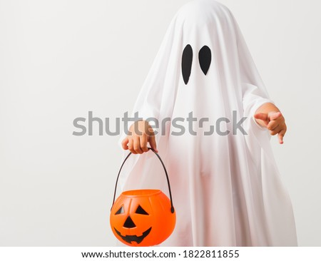 Funny Halloween Kid Concept, little cute child with white dressed costume halloween ghost scary he holding orange pumpkin ghost on hand, studio shot isolated on white background #1822811855