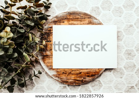 Photo of blank white card on a dark wooden cutting board circle. Blank template for brand identity mock-up design, food theme. Presentation and portfolio template