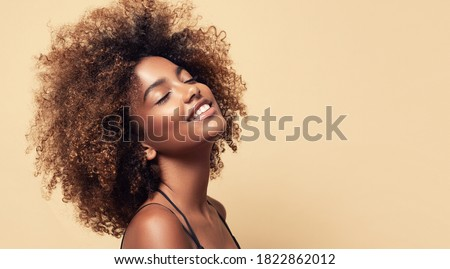 Beauty portrait of african american girl with clean healthy skin on beige background. Smiling dreamy beautiful black woman.Curly  hair in afro style  Royalty-Free Stock Photo #1822862012