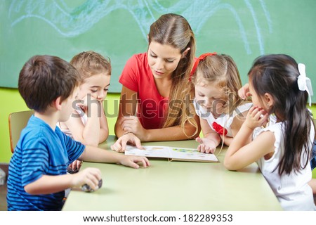 Nursery teacher reading book aloud to children in a kindergarten group