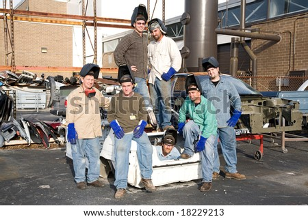 Factory workers surrounded by scrap automobile parts. #18229213