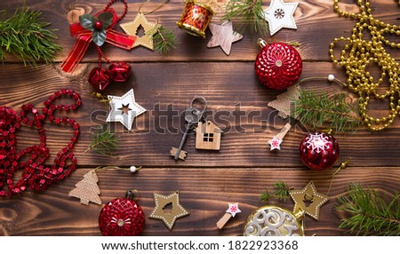 Christmas flat lay on a wooden background with keys to a new house in the center with a place for notes. New year, transfer, shares of the mortgage, the rental of a cottage. Space for text, to do list