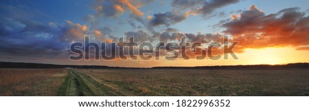 A pathway through the agricultural field under the colorful sunset cumulus clouds after the rain, golden sunlight. Dramatic cloudscape. Idyllic rural landscape. Picturesque panoramic scenery Royalty-Free Stock Photo #1822996352