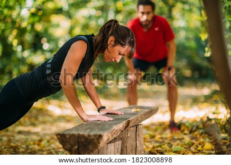 Woman doing push-ups in the park with personal trainer Royalty-Free Stock Photo #1823008898