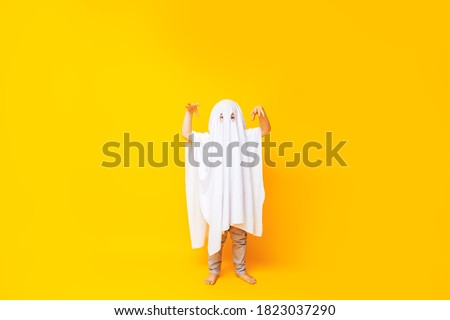 Little kid wearing cute halloween ghost costume on yellow background. Royalty-Free Stock Photo #1823037290