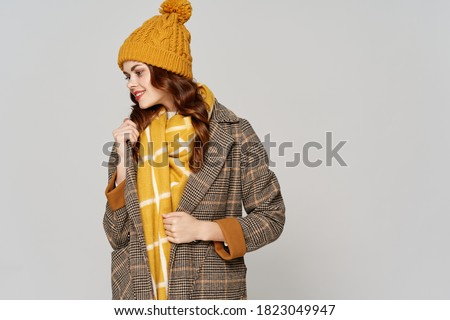 A woman in a yellow hat and a gray coat on a light background Royalty-Free Stock Photo #1823049947