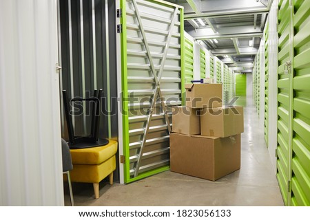 Background image of cardboard boxes stacked by open door of self storage unit, copy space Royalty-Free Stock Photo #1823056133