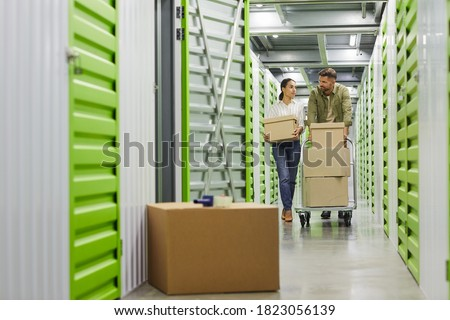 Full length portrait of young couple holding cardboard boxes walking towards camera in self storage unit, copy space Royalty-Free Stock Photo #1823056139
