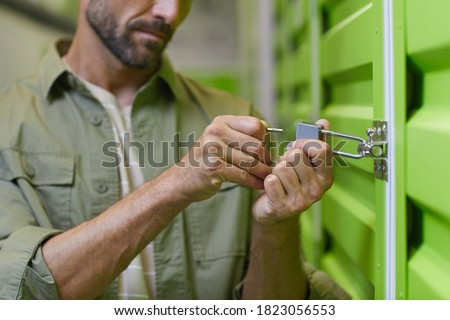 Close up of handsome man opening padlock on door of self storage unit , copy space Royalty-Free Stock Photo #1823056553