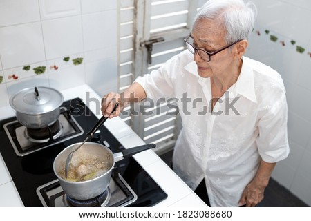 Elderly people cooking vegetables soup or stock in a saucepan and heating the ingredients,healthy food,good cook,asian senior woman standing by the stove in the kitchen at home,concoction concept
