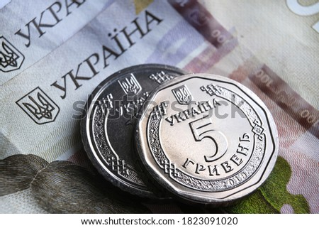 "Ukrainian hryvnia coins placed on 100 UAH bills. New type of coins released in 2019 substitute paper notes. Words seen translated as ""Ukraine"", ""5 Hryvnas"". Royalty-Free Stock Photo #1823091020"