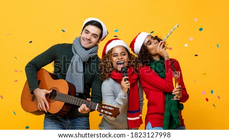 Happy three multiracial friends having party singing and celebrating Christmas in yellow studio background with confetti