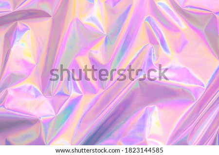 Abstract Modern pastel colored pink holographic background in 80s style. Crumpled iridescent foil textile real texture. Synthwave. Vaporwave style. Retrowave, retro futurism, webpunk Royalty-Free Stock Photo #1823144585