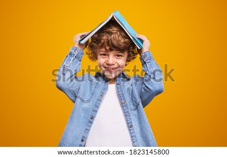 Cheerful child in denim jacket smiling for camera and covering head with book during lesson against yellow background Royalty-Free Stock Photo #1823145800
