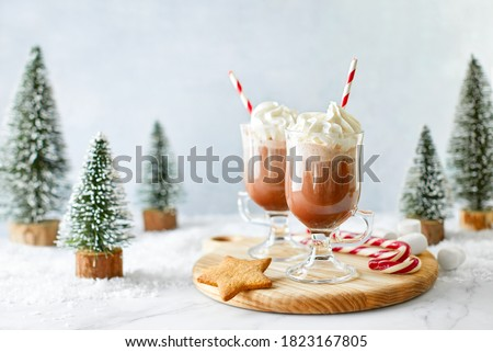 Hot chocolate or coffee with whipped cream  served with a candy cane, marshmallows, and gingerbread star, front view, winter holidays treats concept #1823167805