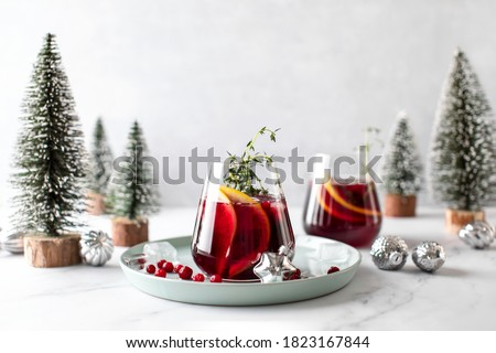 Cranberry gin boozy cocktail with grapefruit and thyme served on winter holidays decorated table, front view #1823167844