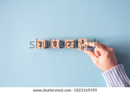 Hand flipping wooden blocks for change year 2020 to 2021 on blue paper background. New year and holiday concept. Royalty-Free Stock Photo #1823169590