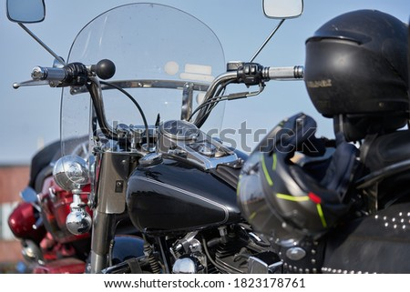 Chrome motorcycle. Stock. Side view of new black motorcycle with chrome details and clothes of motorcyclist lying on it. Chrome details motorcycle reflect landscape of steppe before trip Royalty-Free Stock Photo #1823178761