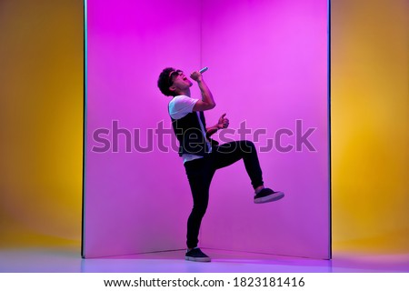 Young male musician, singer performing on pink-orange background in neon light. Concept of music, hobby, festival, entertainment, emotions. Joyful party host, singer, portrait of artist. #1823181416