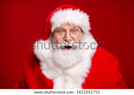Photo of retired old man grey beard open mouth excited look see magical newyear creature make wish bring atmosphere wear santa costume coat spectacles headwear isolated red color background #1823241755