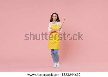 Full length portrait of smiling young brunette woman housewife 20s wearing yellow apron hold rolling pin while doing housework isolated on pastel pink colour background studio. Housekeeping concept Royalty-Free Stock Photo #1823244632