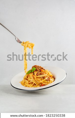 Eating pasta. Egg pasta tagliatelle with bolognese sauce made from meat and tomato sauce. Traditional italian dish from Bologna. Dynamic photo. Minimalism. Light grey background. Copy space. #1823250338