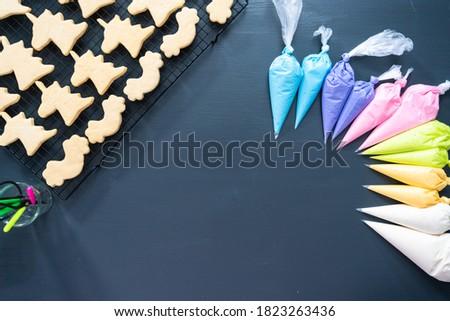 Flat lay. Decorating unicorn sugar cookies with royal icing.