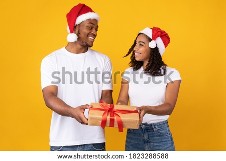 African American Couple Offering Christmas Gift To Camera, Holding Wrapped Xmas Present Box Posing On Yellow Studio Background, Wearing Santa Hats. Winter Holidays Celebration Concept