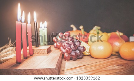Kwanzaa holiday concept with decorate seven candles red, black and green, gift box, pumpkin,corn and fruit on wooden desk and black background.