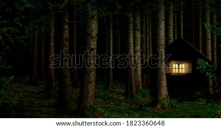 Illuminated window in a cabin in the woods at night Royalty-Free Stock Photo #1823360648