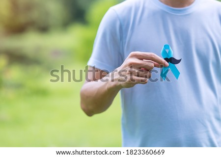November Prostate Cancer Awareness month, adult Man holding Blue Ribbon with mustache for supporting people living and illness. Healthcare, International men, Father and World cancer day concept #1823360669