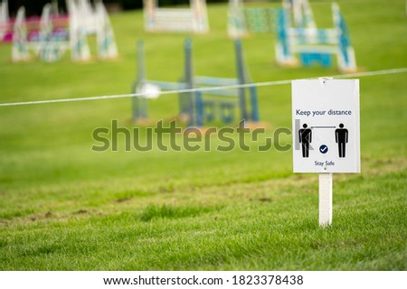 A Covid 19 social distancing sign staked into grass with an horse jumps at an equestrian show jumping outdoor event in the background.