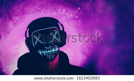 autumn Halloween party, incognito wearing headphones and a glowing mask on a neon purple background Royalty-Free Stock Photo #1823402885